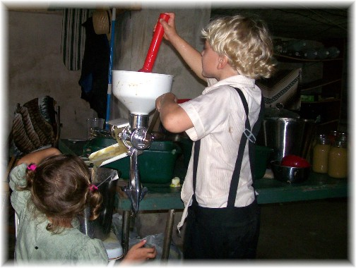 Amish children making apple sauce