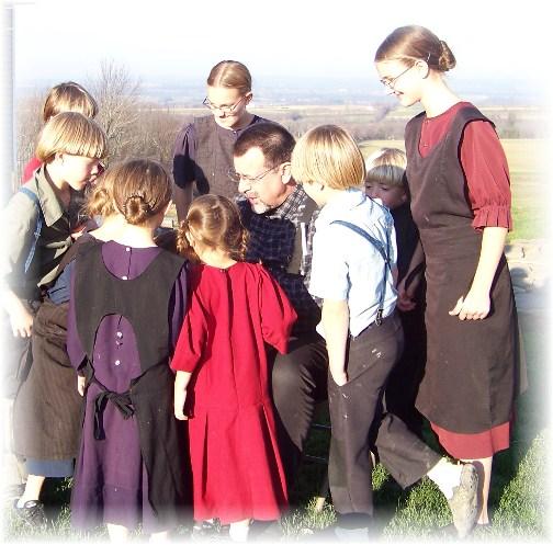 Amish children viewing photos.