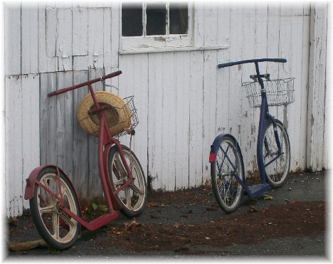 Amish scooters leaning on barn