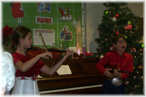 Children playing violins at the Messiah Village Christmas party 2011