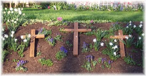 Three crosses in flower bed