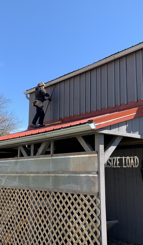 Eli James installing battens on barn