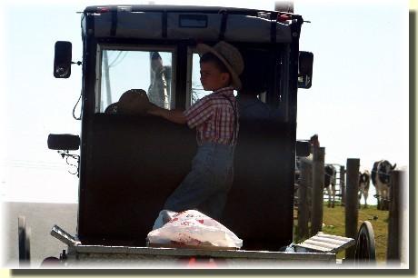 Old order Mennonite boy riding in pickup