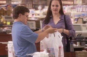 Down Syndrome boy bagging groceries