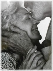 Elderly man kissing woman on forehead
